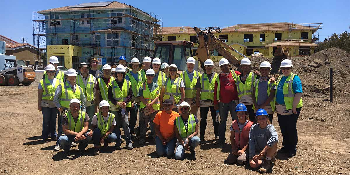 Group photo of volunteers at Habitat for Humanity Build Day standing infront of home being built