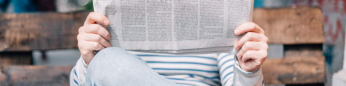 Photo of a person reading a newspaper
